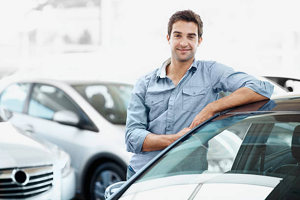 I know exactly which model I'm looking for Smiling young guy standing alongside a car and leaning against it leaning stock pictures, royalty-free photos & images