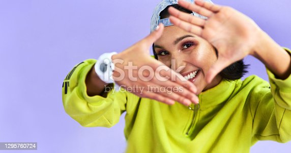 Studio shot of a beautiful young woman making a finger frame gesture against a purple background
