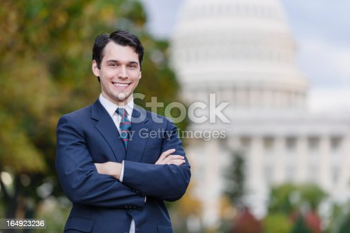 A young politician, staffer, or lobbyist holds with his arms folded, with a confident smile. The United States Capitol building is in the background.