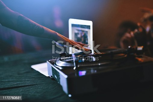 Cropped shot of an unrecognizable female dj mixing music on a turntable in a nightclub