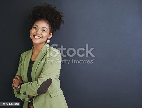 Studio shot of a young woman standing against a dark background