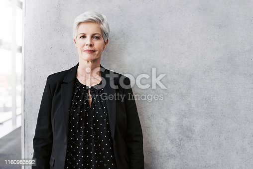 Portrait of a confident mature businesswoman standing against a grey wall