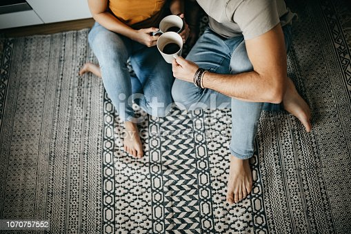 Couple in the kitchen, sitting on the floor and enjoying love