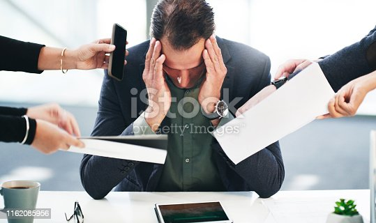 Shot of a mature businessman looking stressed while being overwhelmed with requests from his colleagues in a modern office