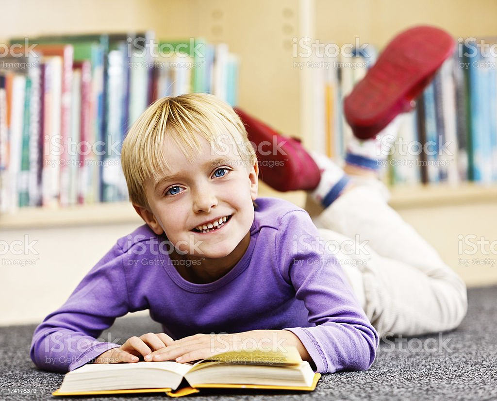 Knowing how to read is great! Smiling girl in library stock photo