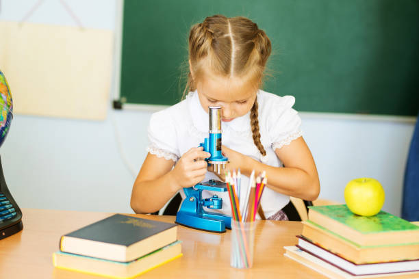 Knowledge is always yours. Little girl study with microscope in classroom stock photo