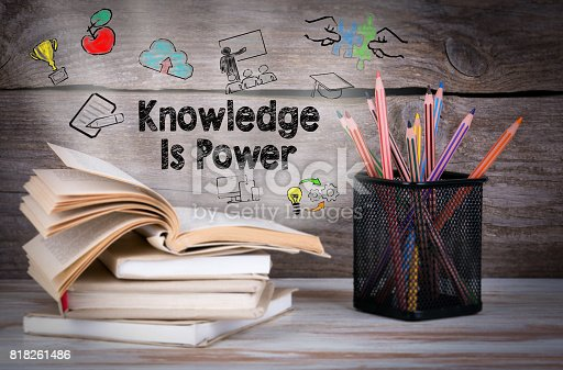 istock Knowledge is power. Stack of books and pencils on the wooden table. 818261486
