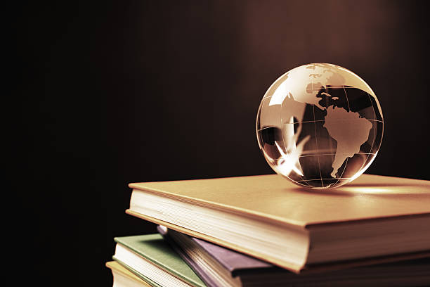 Knowledge of the World Crystal globe on a stack of books, against blackboard background. latin america map stock pictures, royalty-free photos & images