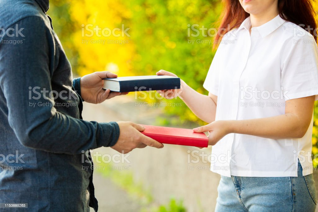 Close up outdoors of two students exchanging books. Knowledge sharing...