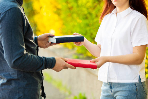 Knowledge sharing between people Close up outdoors of two students exchanging books. Knowledge sharing between people. Give books to read to a friend. borrowing stock pictures, royalty-free photos & images