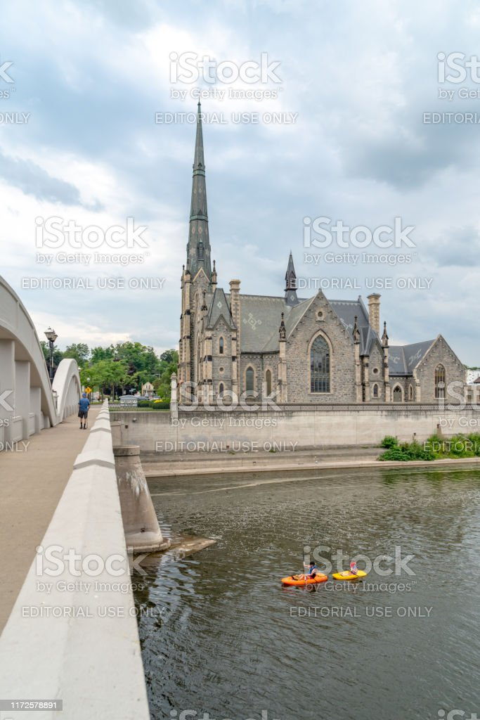 Knox's Galt Presbyterian Church in Cambridge Galt of Ontario, Canada. Tourists are playing canoes on Grand River in Cambridge,Canada. Architecture Stock Photo