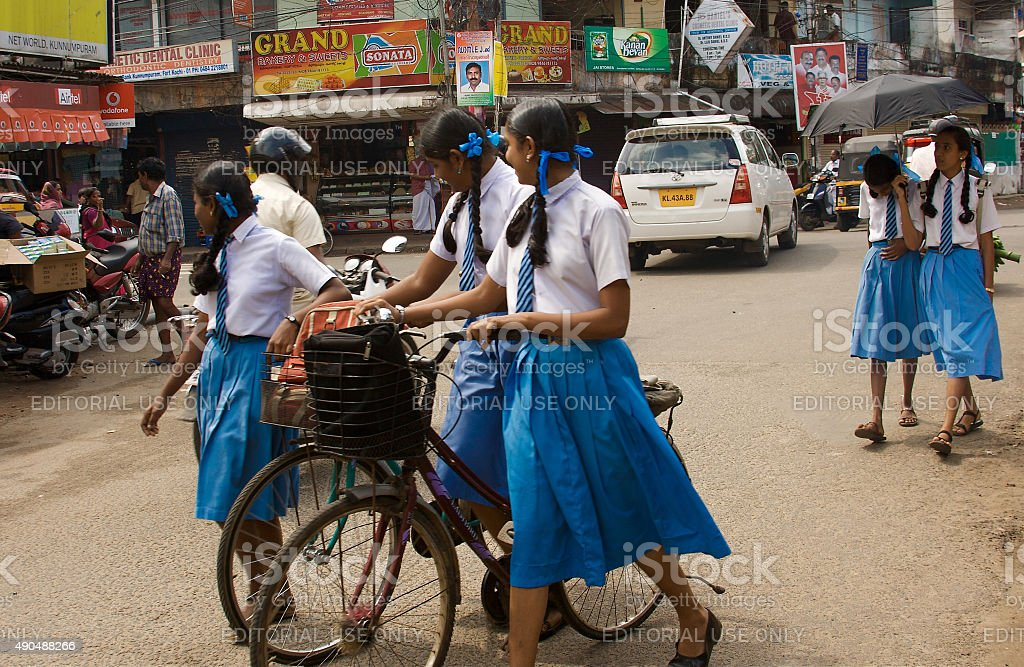 Kochi, India: Street Corner with Students in Uniforms and Bikes stock photo