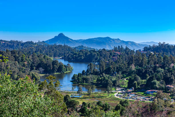 Kodaikanal, South India - Looking Down At Kodaikanal Lake From A Higher Elevation In The Colonial Town In The State Of Tamil Nadu; In The Far Background Is The Peak Known Locally As Perumal Malai. No people. stock photo