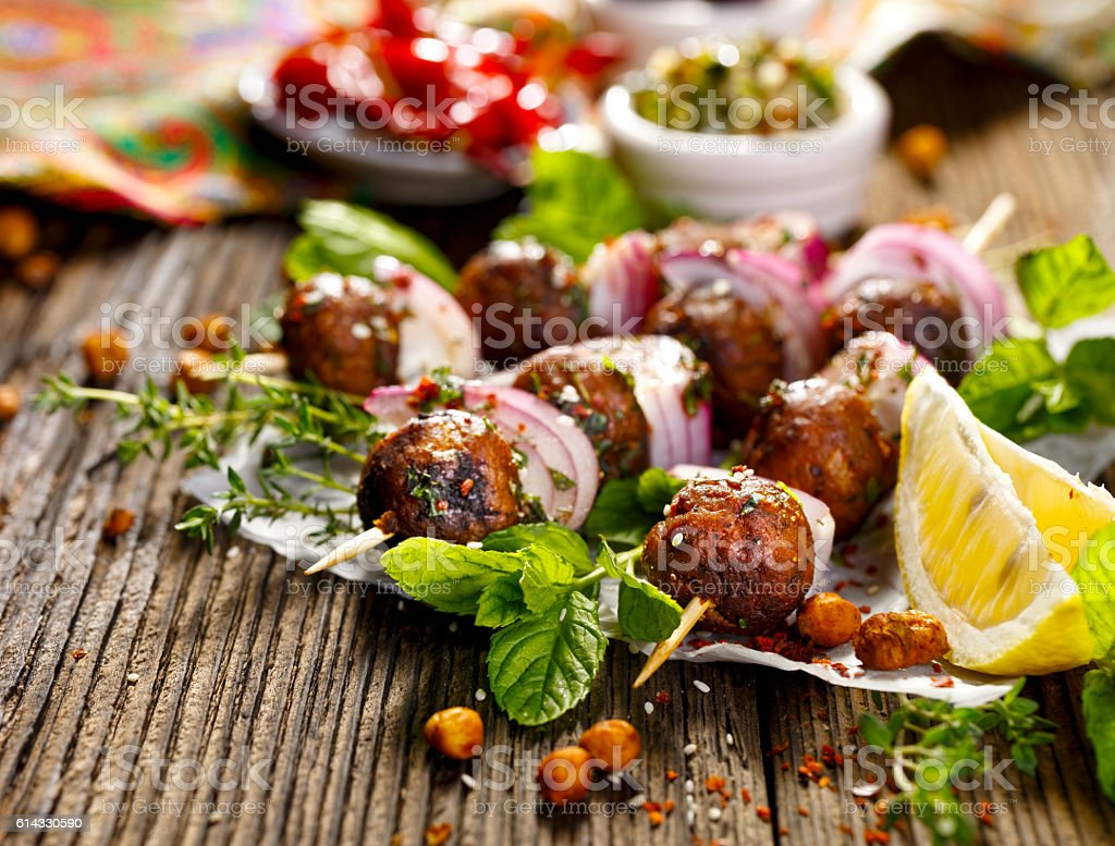 Kofta skewers, meatballs and  onion with addition of fresh herbs stock photo