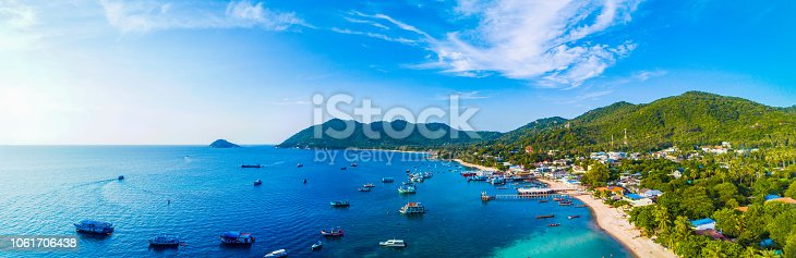 Koh Samui, Thailand - May , 2017:   view showing Koh Tao island, boats on the sea, mountains, houses, trees and people relaxing on the beach with white sands