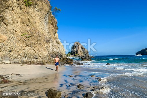A man walking on an idyllic Koka Beach. Hidden gem of Flores, Indonesia. He is enjoying a solo escape. Waves gently washing the shore. There are hills in the back. Happiness, adventure and discovering