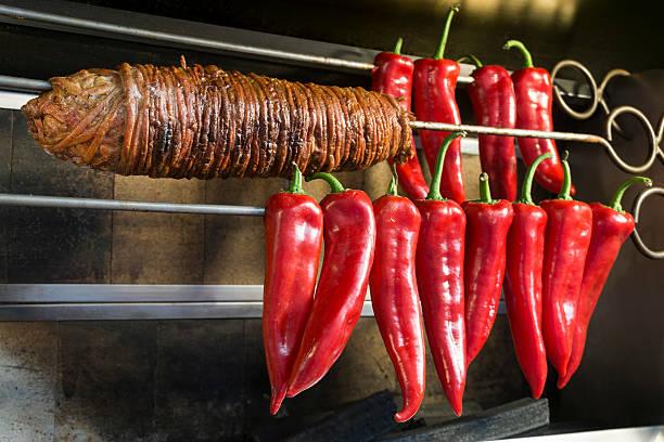 kokorec and some sweet red peppers on a skewer - kokoreç bildbanksfoton och bilder