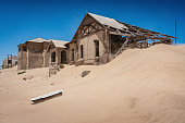 Abandoned half-timbered old historic buildings in Ghost Town Old Diamond Mine und deep blue desert sky. Desert sand dune entering the old abandoned and broken weathered buildings. Kolmanskop, Luderitz, Namibia, Africa.
