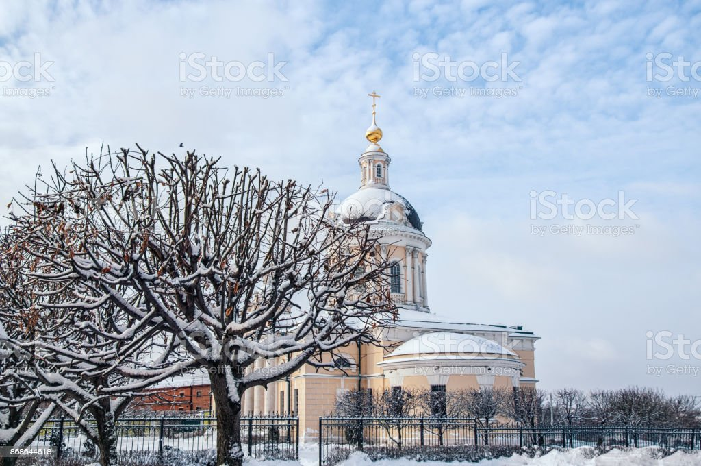 Kolomna Church of the Archangel Michael with a bell tower at dawn with beautiful clouds and Golden light of late autumn in the snow stock photo