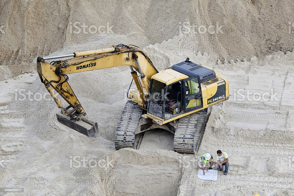 Komatsu excavator and two construction workers on building site. stock photo