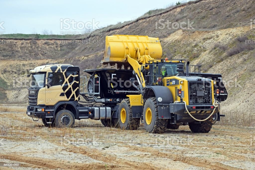 Komatsu loader loading sand into Scania tipper truck stock photo
