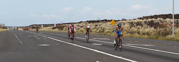 Kona Ironman Triathalon Kona, Hawaii, USA - October 11, 2014:  Ironman athletes during the return bike portion of the annual Kona Ironman triathalon. neicebird stock pictures, royalty-free photos & images