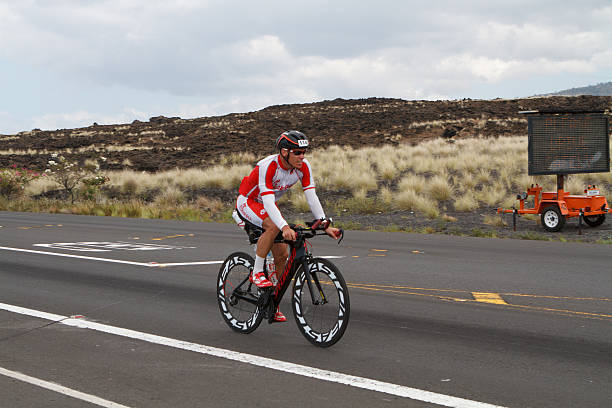 Kona Ironman Triathalon Kona, Hawaii, USA - October 11, 2014: Kona Ironman athlete #1147, Jade Costen (USA), during the return bike portion of the annual Kona Ironman triathalon. neicebird stock pictures, royalty-free photos & images