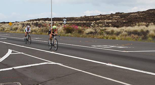 Kona Ironman Triathalon Kona, Hawaii, USA - October 11, 2014: Kona Ironman athlete #2100, Zoe Duffy (AUS), followed by #2209, Chloe Lane also  (AUS), during the return bike portion of the annual Kona Ironman triathalon. neicebird stock pictures, royalty-free photos & images