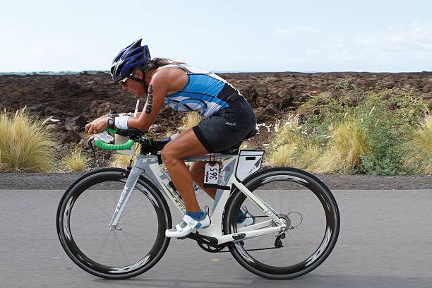 Kona Ironman Triathalon Kona, Hawaii, USA - October 11, 2014: Kona Ironman athlete #365, Cecilia Weber (USA), during the return bike portion of the annual Kona Ironman triathalon. neicebird stock pictures, royalty-free photos & images