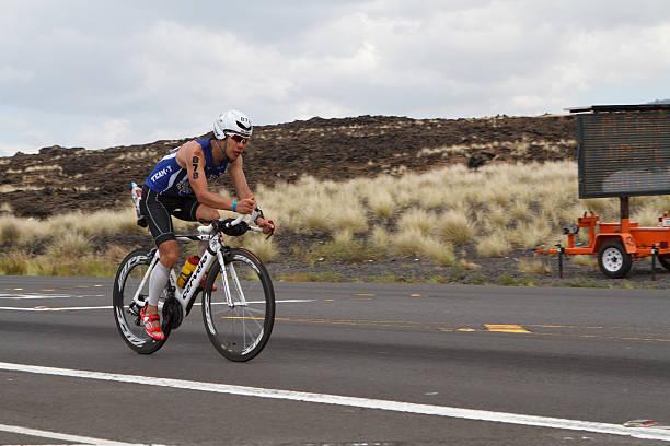 Kona Ironman Triathalon Kona, Hawaii, USA - October 11, 2014: Kona Ironman athlete #878, Yoshihisa Kanayama (JPN), during the return bike portion of the annual Kona Ironman triathalon. neicebird stock pictures, royalty-free photos & images