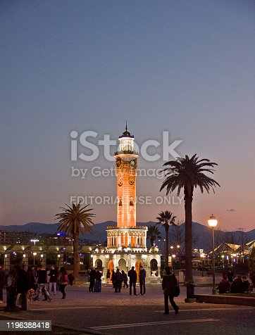 Izmir, Turkey - March 21, 2015: People walk in a park near clock tower at konak square, under the spring moonshine.