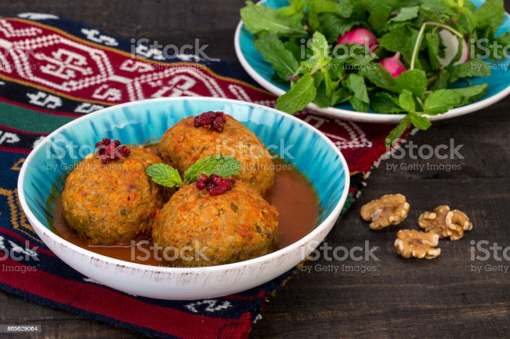 Koofteh Tabrizi Large Meatballs Stuffed With Dried Fruits And Nuts In Tomato Turmeric Broth A Traditional Azeri And Iranian Dish Served In Turquoise Bowl Garnished With Barberries stock photo