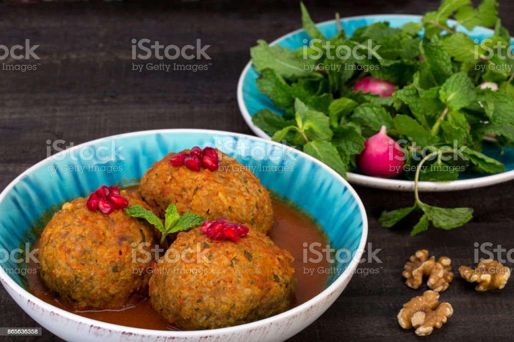 Koofteh Tabrizi Large Meatballs Stuffed With Dried Fruits, Berries And Nuts In Tomato Turmeric Broth A Traditional Azeri And Iranian Dish Served In Turquoise Bowl Garnished With Pomegranate stock photo