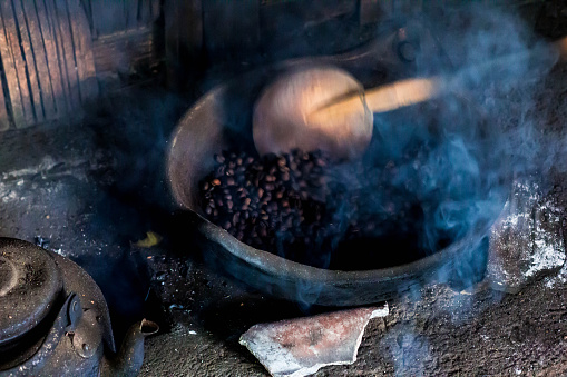 Kopi Luwak Coffee Beans in Indonesian Coffee Roastery. Old Traditional Way of Roasting Raw Coffee Beans on Fire.