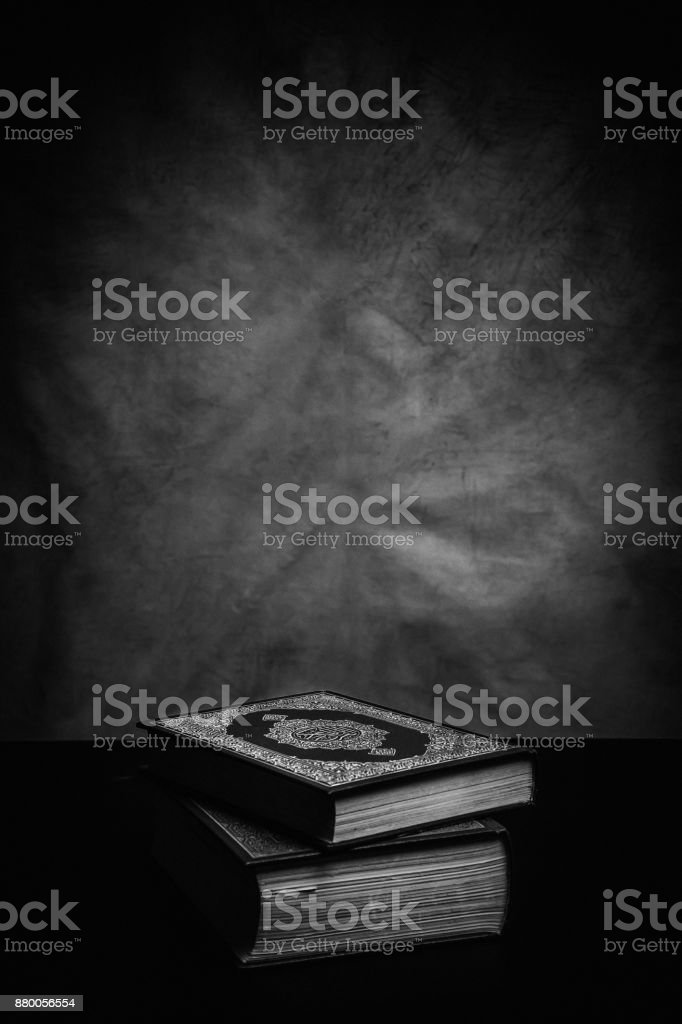 Koran - holy book of Muslims ( public item of all muslims ) on the table , still life . Monochrome or black and white stock photo
