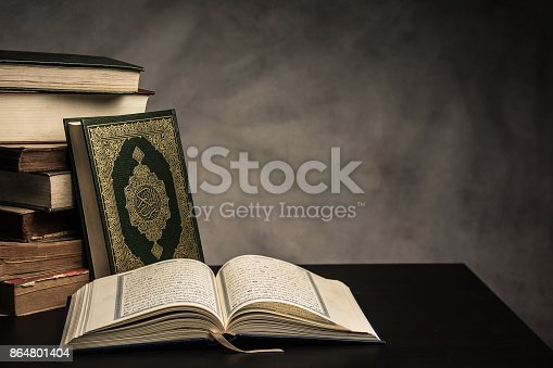 istock Koran - holy book of Muslims ( public item of all muslims ) on the table , still life . 864801404