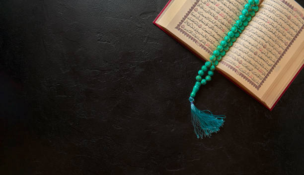koran with rosary beads and muslim hat on black stone or slate texture background - cora��o imagens e fotografias de stock