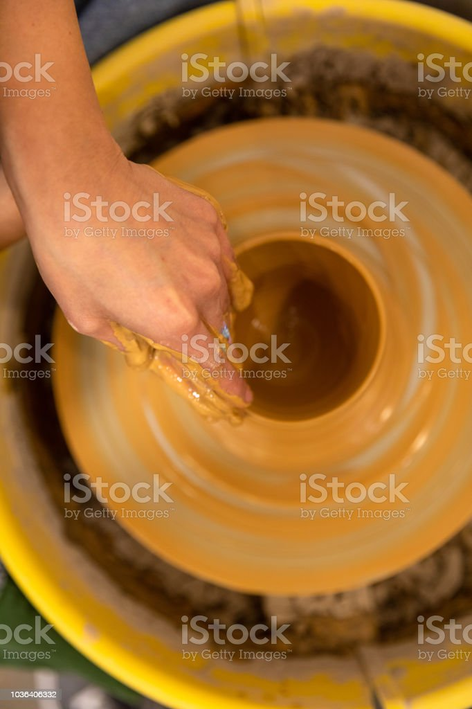 Korean artist molding clay in her small studio shop stock photo
