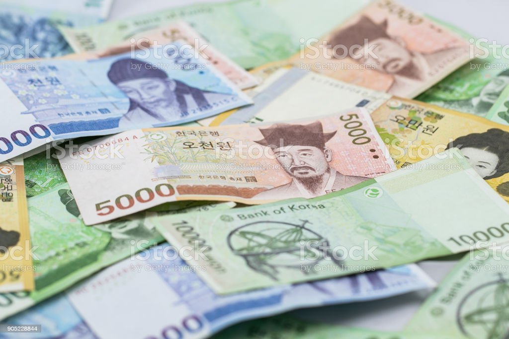 Korean currency.Pile of various currencies isolated on white background. stock photo