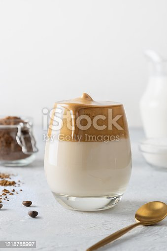 Korean drink Dalgona coffee in glass. Cold milk with foam of instant coffee on white background. Vertical shot.
