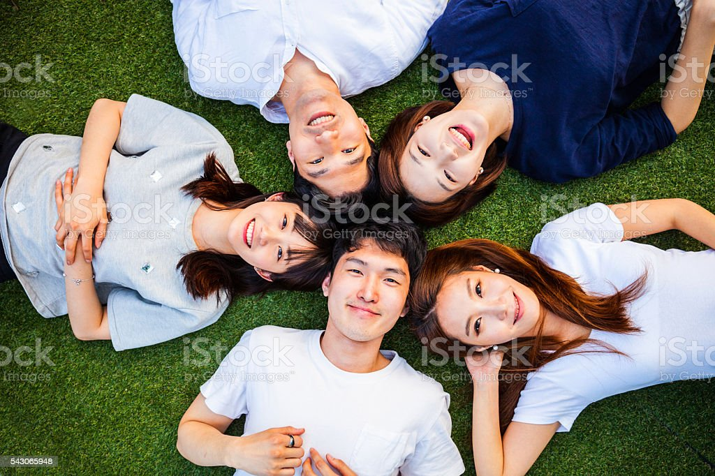 Korean friends having fun and relaxing on the grass stock photo