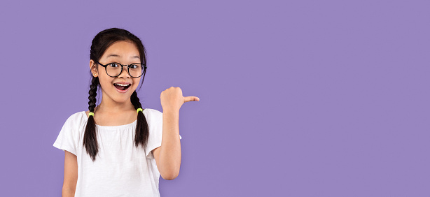 Look There. Excited Korean Kid Girl Pointing Thumb At Free Space For Text Posing On Purple Studio Background. Panorama