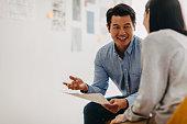 istock Korean graphic designer sharing ideas during meeting in modern office studio 1216308723