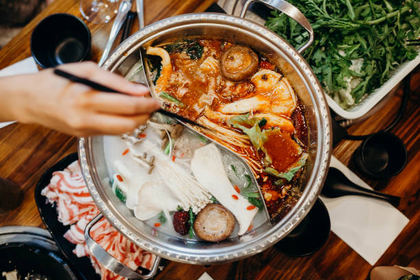 Korean hot pot meal. Hands taking food with chopsticks. stock photo