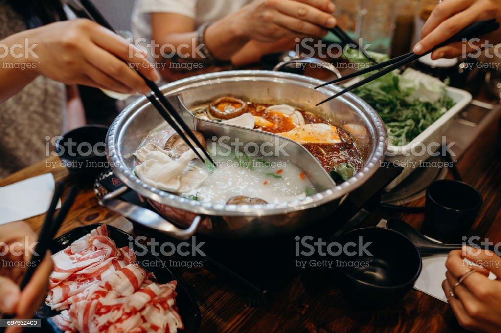 Korean hot pot meal. Hands taking food with chopsticks. stock photo