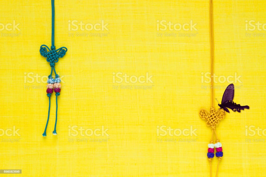 Korean traditional knot & butterfly background of yellow ramie fabric. stock photo
