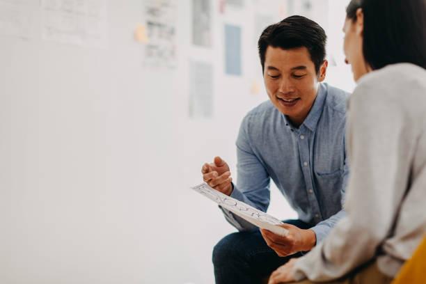 Korean web designer sharing ideas during meeting in modern office studio stock photo