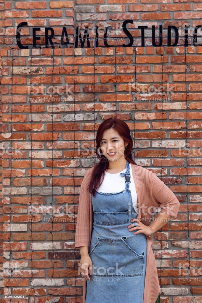 Korean woman artist posing in her small business handcraft and clay studio in Seoul stock photo