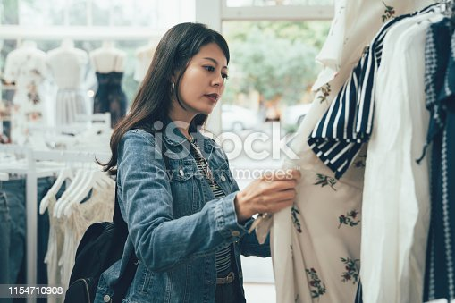 Young korean woman looking through new clothes during shopping in dress store on christmas sale. asian female know fashion love buying trendy products. elegant shopper indoors in shop mall center.