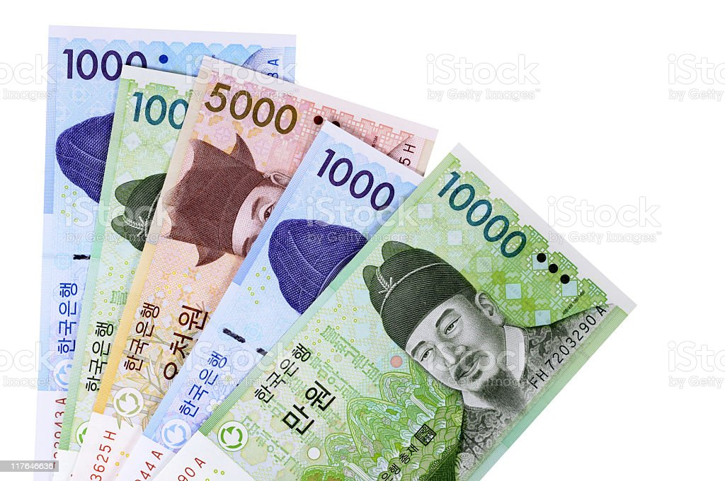 Korean Won currency bills are fanned out on a white surface stock photo